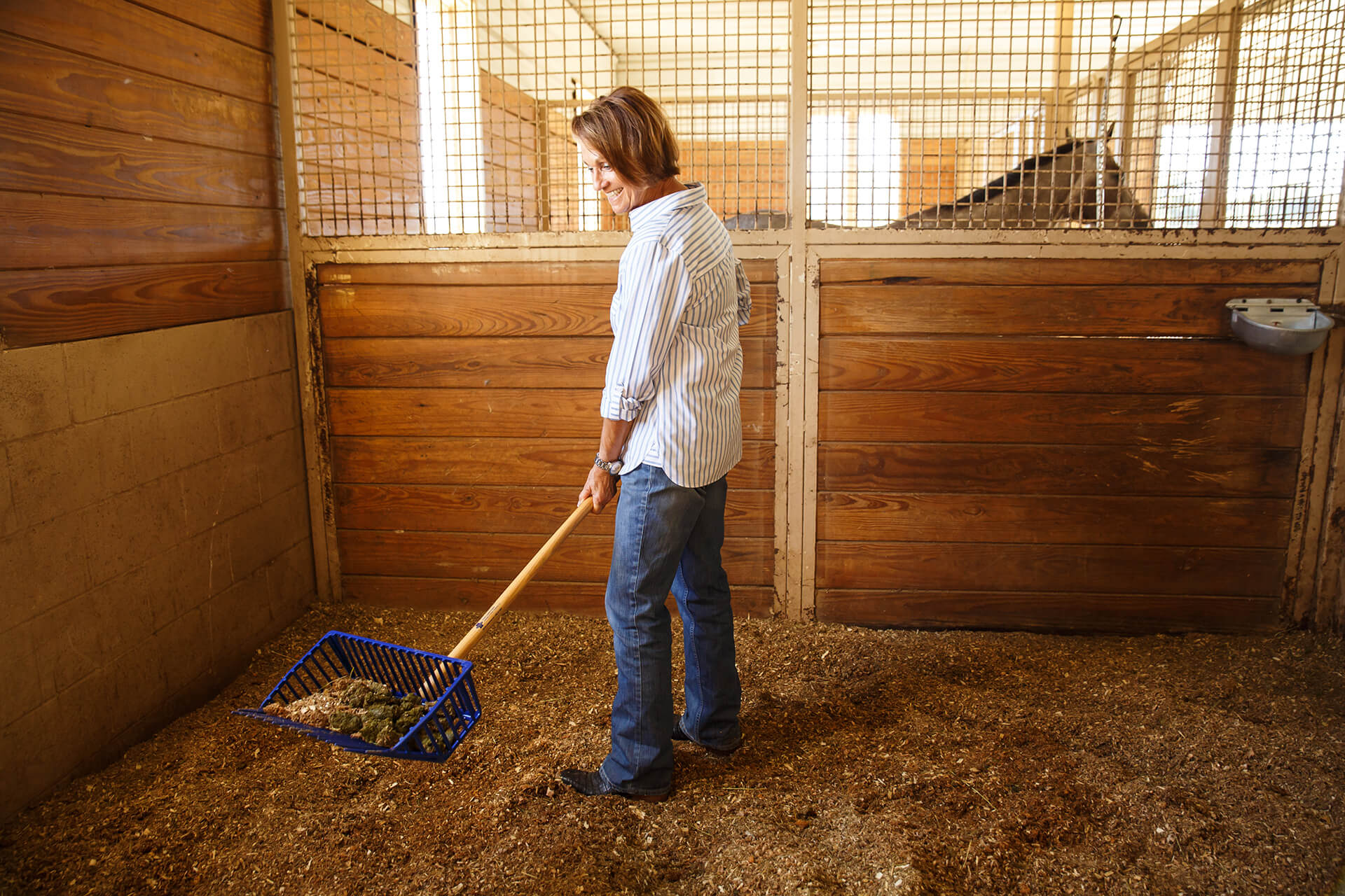 woman scooping manure