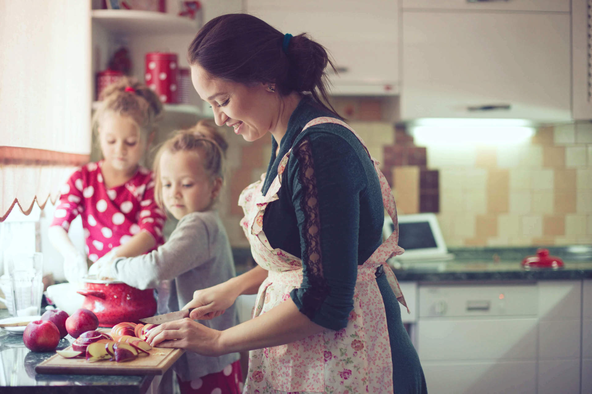 Mother slicing apples with daughters